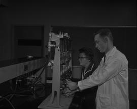Food Processing Technology, 1966; student in lab coat and instructor using food processing equipm...