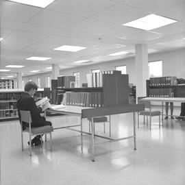 BCIT Library ; man sitting at a desk reading a book ; people in background