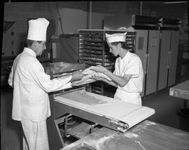 BC Vocational School Cook Training Course ; instructor and a student flattening dough using an in...