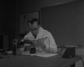 Instrumentation, 1966; man in a lab coat sitting at a desk and soldering a piece of equipment