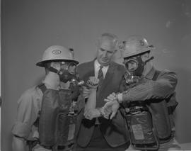 Mining, 1966; two men wearing protective mining gear ; a man in a suit checking the pulse of one ...