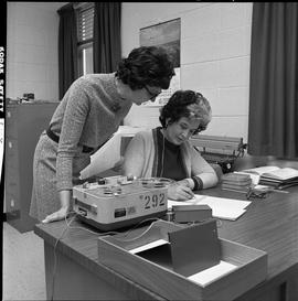 BC Vocational School Commercial Program; student transcribing by hand recorded information from a...