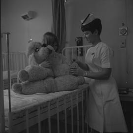 Nursing, 1968; a nurse talking to a child sitting on a bed holding a teddy bear
