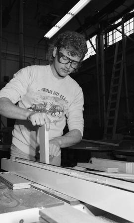BCIT Carpentry, 1989, man wearing eye protection cutting wood [1 of 7 photographs]