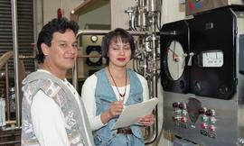 Male and female First Nations students standing near a milk pump pasteurizing equipment [3 of 4 p...