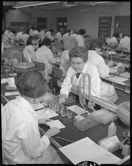 Medical laboratory technology, 1967; instructor talking to a student in a classroom filled with s...
