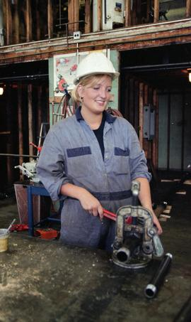 BCIT Women in Trades; plumbing, woman with pipe (cutting?) machine, September 1, 1995 [2 of 9 pho...