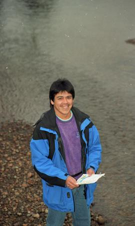 Male First Nations BCIT graduate standing outside holding a notebook [10 of 16 photographs]