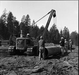Heavy duty equipment operator, Nanaimo ; group of men standing next to a large pipe ; man operati...