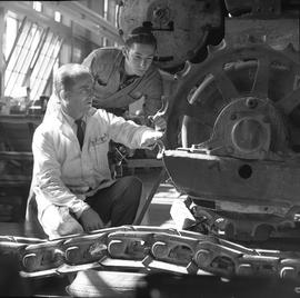 Logging, 1969; two men looking at mechanical parts of logging equipment