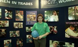"BCIT open house '98, Woman with a hard hat standing in front of a ""Women in Trades"" pos..."