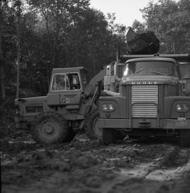 Logging, 1969; man driving a payloader moving dirt into a dump truck