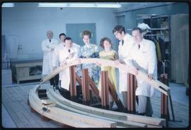 Forest Products; two women and five men wearing lab coats holding a large piece of lumber in a wo...
