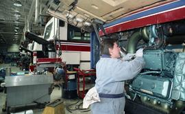 BCIT women in trades; BC Transit, students wearing uniforms while using tools on auto parts insid...