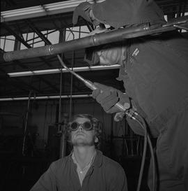 Welding, Terrace, 1968; man welding a thin pipe, another man wearing protective goggles crouched ...