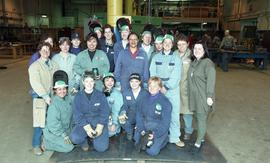 Trades discovery for women; steel fabrication, group shot of students in uniforms inside a shop [...