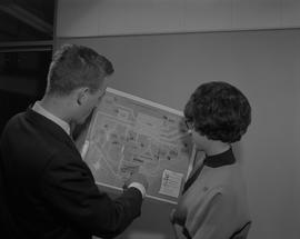 Business Management; a man and a woman looking at a flow chart titled 'Flow and costs of assets t...
