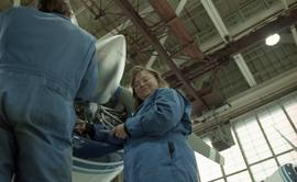 Canadian women at work; woman in uniform working on a jet engine with tools inside a hangar [3 of...