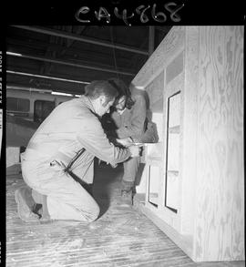 B.C. Vocational School; Carpentry Trades instructor measuring a shelving unit with a student obse...