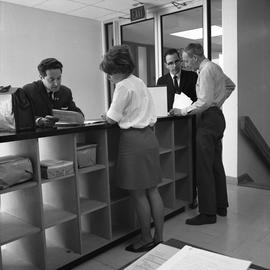 BCVS Graphic arts ; four people standing at a shelf and looking at papers [1 of 3]