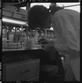 Medical laboratory technology, 1968; student in lab coat examining a glass slide