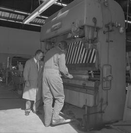 Sheet metal, 1968; instructor watching a student using machinery to shape a piece of sheet metal ...