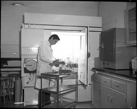 BCIT Food Technology program ; a student examining plants in a refrigerator and writing notes on ...