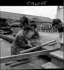 B.C. Vocational School; Carpentry Trades instructor and student examining a piece of lumber that ...