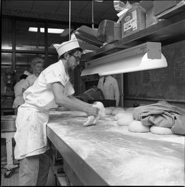 BC Vocational School Cook Training Course ; student rolling dough ; students in background