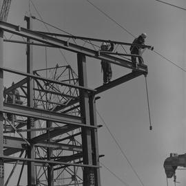 Structural steel, 1971; two workers standing on a side beam guiding a large piece of steel