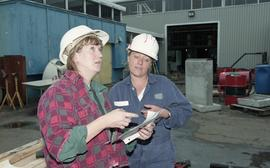 Trades discovery for women; piping, students in helmets and uniforms using piping tools and equip...