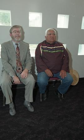 Staff member sitting down beside First Nations elder during First Nations graduation