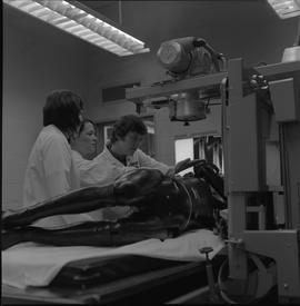 Medical radiography, 1968; three people in lab coats adjusting an x-ray machine with a manikin la...