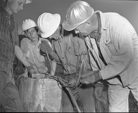 Logging, 1967; four men wearing hard hats repairing a lifting cable