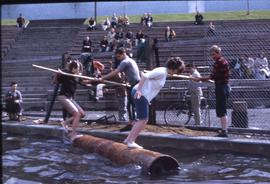 Lumberjack event; two women in a logrolling competition and two men standing on the side of the w...