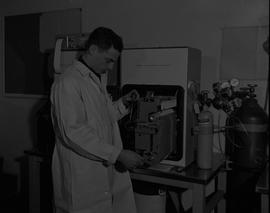 Instrumentation, 1964; man in a lab coat using a screwdriver to repair a vapor fractometer record...