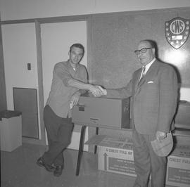 Heavy Duty presentation, 1970; two men shaking hands standing next to a toolbox