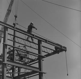 Structural steel, 1971; man walking along a beam at the top of a steel structure