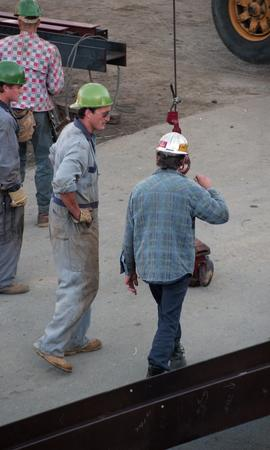Ironwork, students wearing tool belts, hard hats and uniforms standing around a construction vehi...