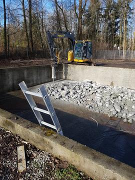 BCIT Lumberman's pool with fence removed, bobcat with jackhammer attachment working, ladder into ...