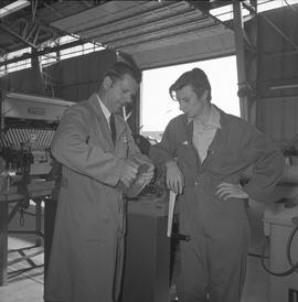 Sheet metal, 1968; two men looking at a cylinder piece of sheet metal ; tools in background