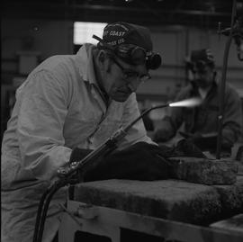 Welding, 1968; man looking at item he welded, welding torch turned on and resting on a holder nex...