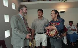 Man holding speech (?) for the First Nations graduation talking with a First Nations man holding ...