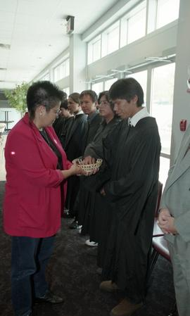 First Nations (?) woman presenting a wooden bowl filled with stones to each graduate [1 of 2 phot...