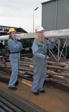 BCIT women in trades; plumbing, students in uniforms and hard hats carrying piping material [8 of...