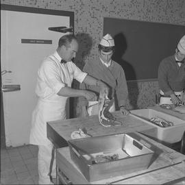 Meat cutting, 1968;  an instructor demonstrating how to cut meat for a student ; student working ...