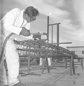 Structural steel, 1971; worker welding part of a steel structure