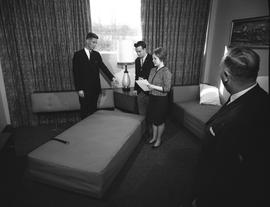 Hotel Motel, 1964; three men and a woman standing in a staged hotel room examining a bed, the wom...