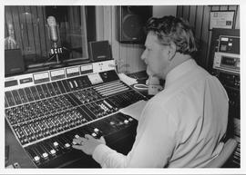 Broadcast Communication; man in a white dress shirt sitting at the control board in the radio con...