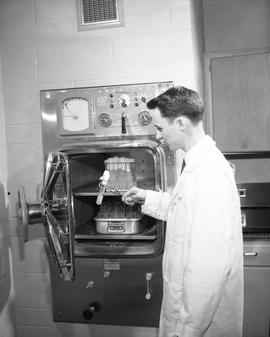 Food Processing Technology; man in a lab coat removing a test tube from food processing equipment
